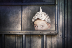 Boy in a tinfoil hat peeking out window bs